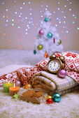 Composition with plaids, candles and Christmas decorations, on white carpet on bright background — Stock fotografie