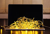 Laptop with garland, on office interior background — Foto de Stock
