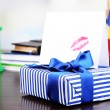Stock Photo: Gift with card for loved one on desktop on room background