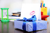 Gift with card for loved one on desktop on room background — Stock Photo