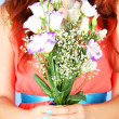 Woman holding bouquet, on blue background, close-up — Stock Photo