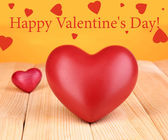 Decorative red hearts on wooden table on orange background — Stock Photo