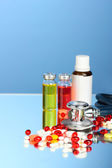 Medicines and a stethoscope on a blue background close-up — Stock Photo
