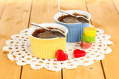 Chocolate pudding in bowls for baking on wooden table — Stock Photo