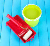 Set for painting: paint pot, paint-roller on blue wooden table — Stock Photo