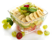 Tasty fruit salad in glass bowl, isolated on white — Stock Photo