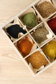 Assortment of spices in wooden box, on wooden background — Stock Photo