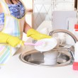 Beautiful young woman washing dishes in kitchen — Stock Photo #37850583
