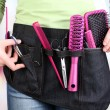Womhairdresser with tool belt on bright background — Stock Photo #37850529