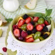 Fruit salad in plates on wooden table near napkin — Stock Photo