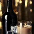Baileys liqueur in bottle and glass on golden background — Stockfoto