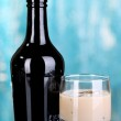 Baileys liqueur in bottle and glass on blue background — Stockfoto