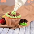 Stock Photo: Confectioner decorating tasty cupcake with butter cream, on color wooden table, on lights background