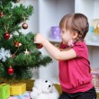 Little girl sitting near Christmas tree in room — Stock Photo #37852245