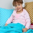 Stock Photo: Little girl sitting on pillows on wall background