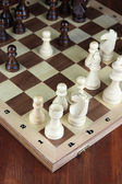 Chess board with chess pieces on wooden table close-up — Foto Stock