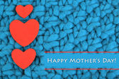 Hearts made of felt on blue knitted background — Stock Photo