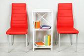 Krásný interiér s moderní barevné židle, knihy o dřevěný stojan na zeď na pozadí — Stock fotografie