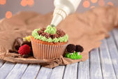 Confectioner decorating tasty cupcake with butter cream, on color wooden table, on lights background — Stock fotografie