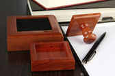 Wooden stamp with clipboard and books on table — Stock Photo