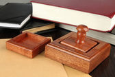 Wooden stamp with notepads and books on table — Stock Photo