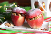 Stuffed Christmas apples with nuts and raisins on table on wooden background — Stock Photo