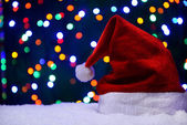 Santa hat on snow on lights background — Stock Photo