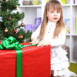 Little girl with big present box near Christmas tree in room — Stock Photo #37903037