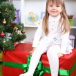 Little girl setting on big present box near Christmas tree in room — Stock Photo #37903045
