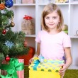 Little girl holding present box near Christmas tree in room — Stock Photo