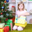 Little girl holding present box near Christmas tree in room — Stock Photo #37903071