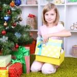 Little girl holding present box near Christmas tree in room — Stock Photo