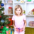 Little girl holding present box near Christmas tree in room — Stock Photo #37903083