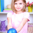 Little girl holding Christmas ball in room — Stock Photo