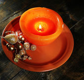 Burning candle with Christmas decorations on color plate, on wooden background — Stock Photo