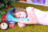Little girl sleeping near Christmas tree in room — 图库照片