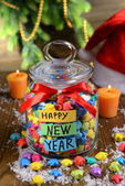 Paper stars with dreams in jar on table on wooden background — Stock Photo