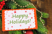 Christmas card on fir branch on wooden background — Stock Photo