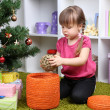 Little girl with Christmas ball near fir tree in room — Stock Photo