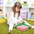 Little girl with present box near Christmas tree in room — Stock Photo #37925537