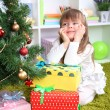 Little girl with presents near Christmas tree in room — Stock Photo #37925541