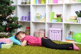 Little girl sleeping near Christmas tree in room — Foto de Stock