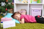 Little girl sleeping near Christmas tree in room — Stock Photo