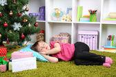 Little girl sleeping near Christmas tree in room — Foto Stock