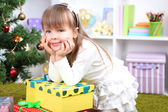 Little girl with presents near Christmas tree in room — Stockfoto