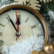 Clock with fir branches and Christmas decorations under snow close up — Stock Photo #37932465