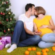 Young pregnant woman with her husband sitting on floor near Christmas tree at home — Stock Photo #37932545