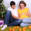 Young pregnant woman with her husband sitting on floor near Christmas tree at home — Stock Photo #37932559