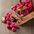 Stock Photo: Ripe sweet raspberries in basket on wooden background