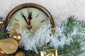 Relógio com abeto ramos e decorações de Natal sob a neve de perto — Fotografia Stock